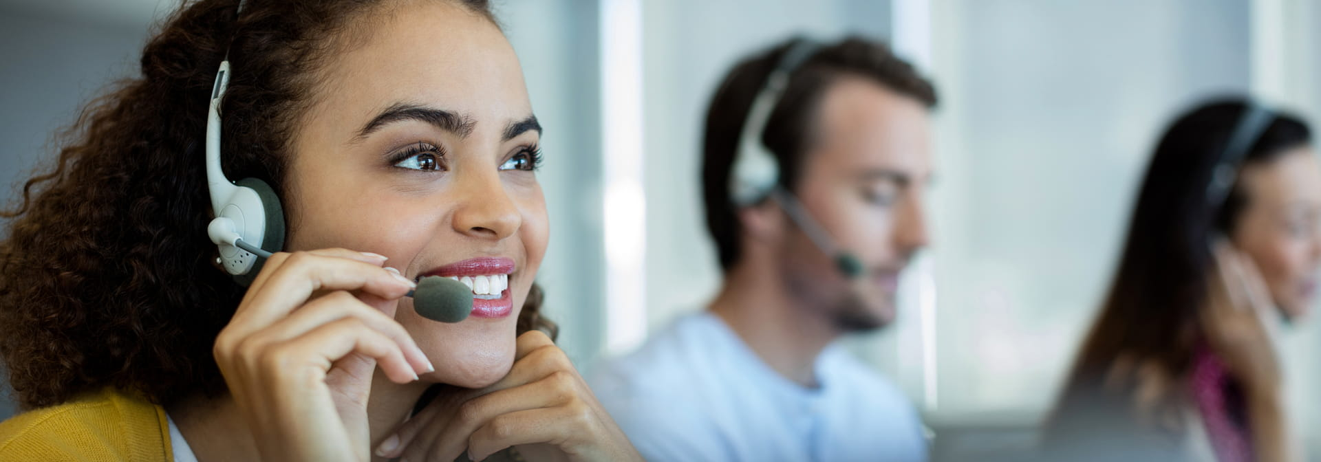 Three people with headsets in a call center
